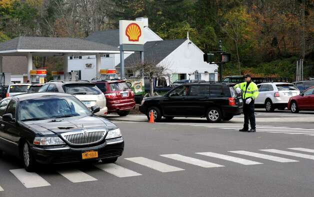 Officer Craig Zottola directs traffic as a controlled chaos ensued at the Shell station at Glenville Road and Weaver Street in the Glenvlle section of Greenwich. New Jesrey, New Yorkers and Conn. residents descended on the area to fill up tanks and containers on Friday, Nov. 2, 2012. Photo: Cathy Zuraw / Greenwich Time
