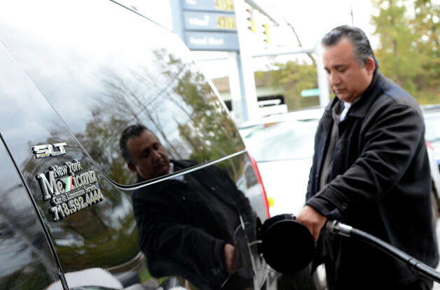 Genaro Perez, a limo driver from Queens, N.Y., fills up his car at the Shell gas station on West Ave. in Stamford after dropping off a client on Friday, Nov. 2, 2012. The gas station closed the entrance on West Ave. to better control the flow of traffic into the station. Cars were forced to enter the station on Grenhart Rd. Controlled chaos ensued at Stamford gas stations as New Yorkers and Conn. residents descend on the area to fill up tanks and containers. A run on Stamford and Greenwich gas stations by fuel-starved New York and New Jersey residents continued Friday, Nov. 2, 2012. Traffic jams were common around some of the more popular stations in downtown Stamford and those open by Interstate-95. Photo: Amy Mortensen / Connecticut Post Freelance
