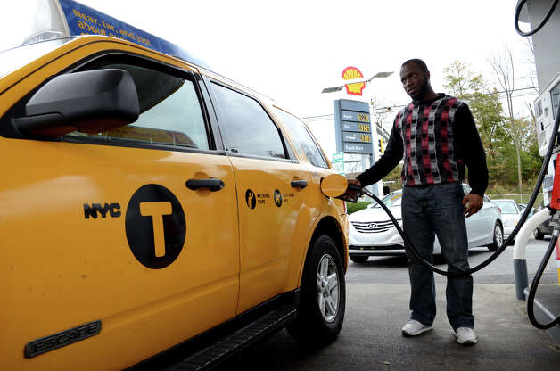 New York taxi driver Mussa Ousucc, of the Bronx, N.Y., fills up at the Shell gas station on West Ave. in Stamford on Friday, Nov. 2, 2012. The gas station closed the entrance on West Ave. to better control the flow of traffic into the station. Cars were forced to enter the station on Grenhart Rd. Controlled chaos ensued at Stamford gas stations as New Yorkers and Conn. residents descend on the area to fill up tanks and containers. A run on Stamford and Greenwich gas stations by fuel-starved New York and New Jersey residents continued Friday, Nov. 2, 2012. Traffic jams were common around some of the more popular stations in downtown Stamford and those open by Interstate-95. Photo: Amy Mortensen / Connecticut Post Freelance