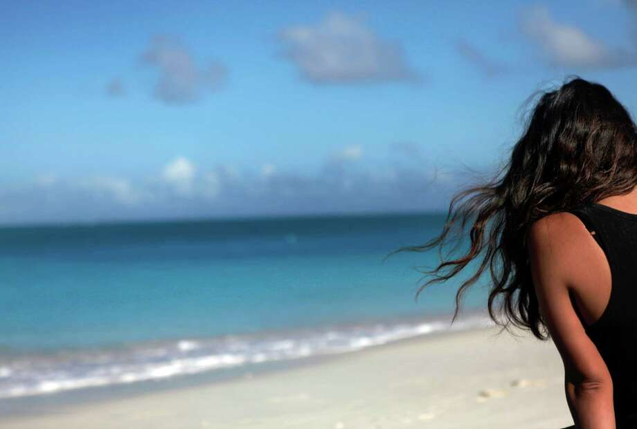 FILE-- A woman sits on the beach at the Club Med Turkoise on the Turks and Caicos Islands, Jan. 12, 2012. Being alone doesn?t mean being lonely when you can travel solo over the holidays with city explorations, sunny getaways, adventure outings and educational or volunteer trips. (Beatrice de Gea/The New York Times) -- PHOTO MOVED IN ADVANCE AND NOT FOR USE - ONLINE OR IN PRINT - BEFORE NOV. 04, 2012. -- Photo: BEATRICE DE GEA / NYTNS