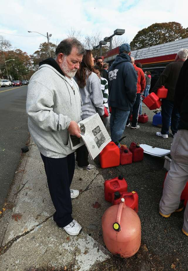 SEAFORD, NY - NOV. 2:  In the aftermath of Superstorm Sandy, Richard Campbell of Seaford reads the paper while waiting for gas in line on Nov. 2, 2012 in Seaford, New York. This station had one line for cars and one for walkers with containers. With the death toll continuing to rise and millions of homes and businesses without power, the U.S. east coast is attempting to recover from the effects of floods, fires and power outages brought on by Superstorm Sandy.  (Bruce Bennett/Getty Images) Photo: Bruce Bennett, Getty Images / 2012 Getty Images