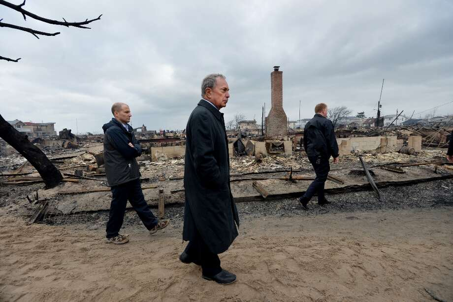 New York City Mayor Michael Bloomberg (C) views damage in the Breezy Point area of Queens in New York on October 30, 2012 after fire destroyed about 80 homes as a result of Hurricane Sandy which hit the area on October 29. The death toll from superstorm Sandy has risen to 35 in the United States and Canada, and was expected to climb further as several people remained missing, officials said. Officials in the states of Connecticut, Maryland, New York, New Jersey, North Carolina, Pennsylvania, Virginia and West Virginia all reported deaths from the massive storm system, while Toronto police said a Canadian woman was killed by flying debris.    (Stan Honda/AFP/Getty Images) Photo: STAN HONDA, AFP/Getty Images / AFP