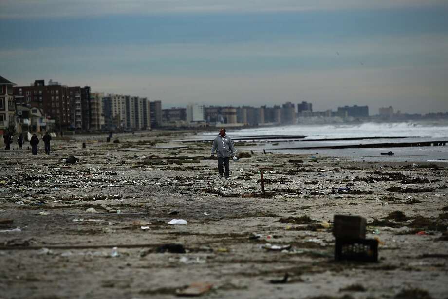 NEW YORK, NY - NOV. 2: A man walks along the beach in the heavily damaged Rockaway neighborhood, in Queens where a large section of the iconic boardwalk was washed away on November 2, 2012 in New York, United States. Limited public transit has returned to New York and most major bridges have reopened but will require three occupants in the vehicle to pass. With the death toll currently over 70 and millions of homes and businesses without power, the US east coast is attempting to recover from the effects of floods, fires and power outages brought on by superstorm Sandy.  (Spencer Platt/Getty Images) Photo: Spencer Platt, Getty Images / 2012 Getty Images