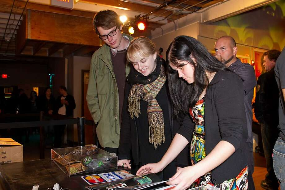 "What's a heavy metal event without a few souvenirs? Jacob McNamara, Robyn Miller and Natelie Barringer browse Kirk Hammett's new book at the book launch party for ""Horror Business,"" held Nov. 1 at Public Works nightclub. Photo: Drew Altizer Photography"