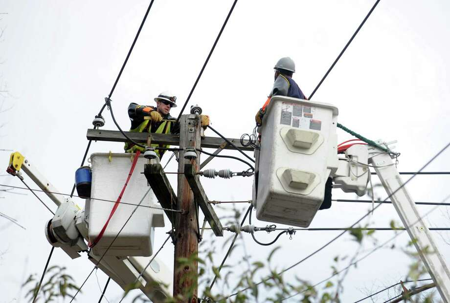 Brian Goodness, left, and Dave Bruce, utility workers from Massachusetts, repair lines on Sturges Road in Fairfield, Friday, Nov. 2, 2012. Photo: Autumn Driscoll / Connecticut Post