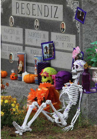 A grave is decorated with skeletons on the Catholic feast known as All Soul's Day, Friday, Nov. 2, 2012. The grave is located at San Fernando Cemetery No. 2. Families have made pilgrimages to the West Side cemetery each Nov. 2 since its opening in 1922 — to decorate graves, leave offerings and pray for the departed. Photo: John Davenport, San Antonio Express-News / ©San Antonio Express-News/Photo Can Be Sold to the Public