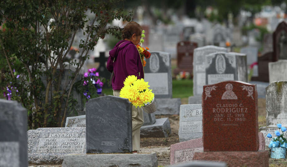 Guadalupe Garcia brings flowers to her uncle's grave on the Day of the Dead Friday, Nov. 2, 2012, at San Fernando Cemetery No. 2. Photo: John Davenport, San Antonio Express-News / ©San Antonio Express-News/Photo Can Be Sold to the Public