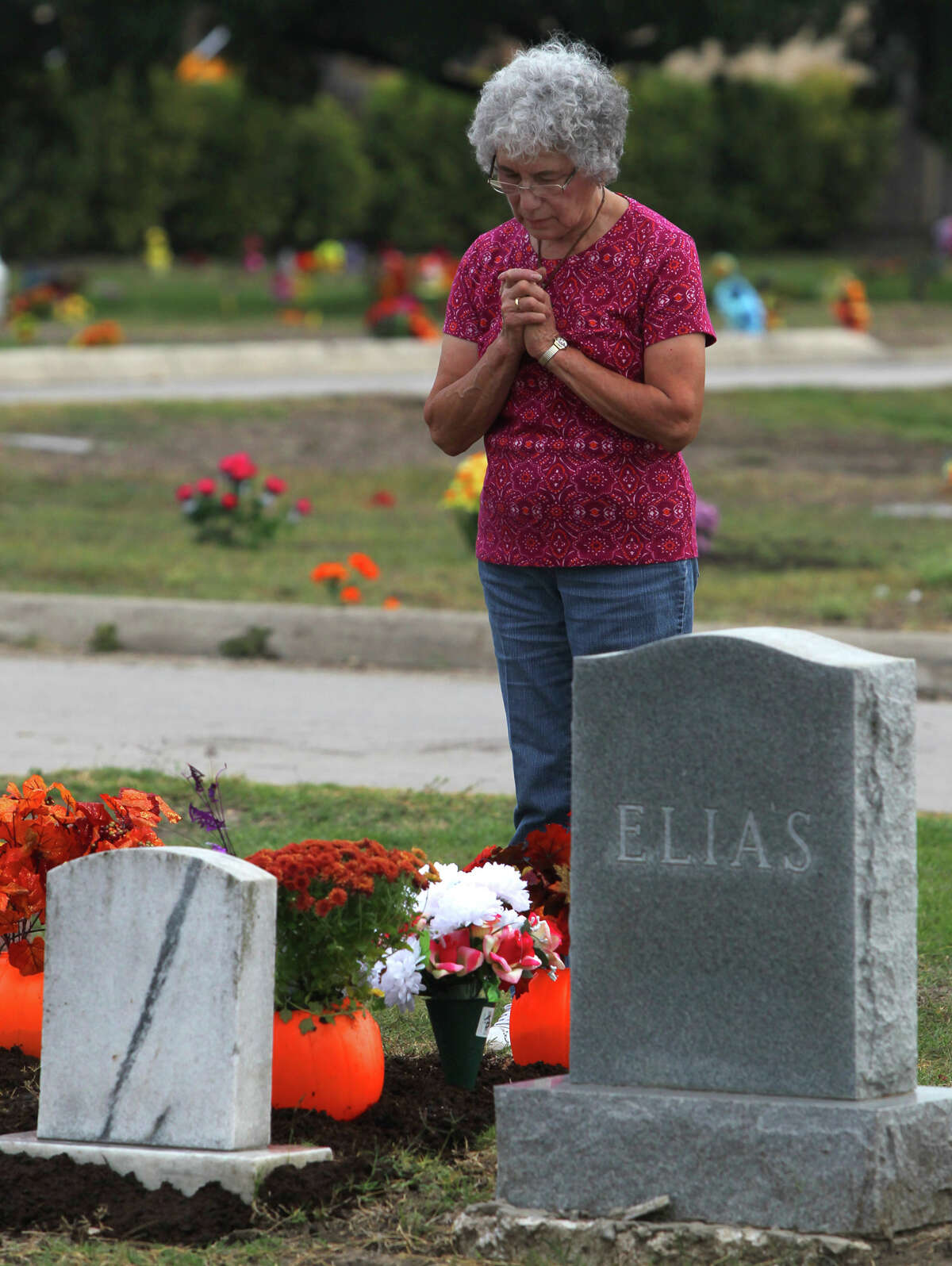 Elisa Van Tine prays at the graves of her mother and grandmother at San Fernando Cemetery No. 2 on the Catholic feast known as All Soul's Day or Dia de los Muertos Friday, Nov. 2, 2012.