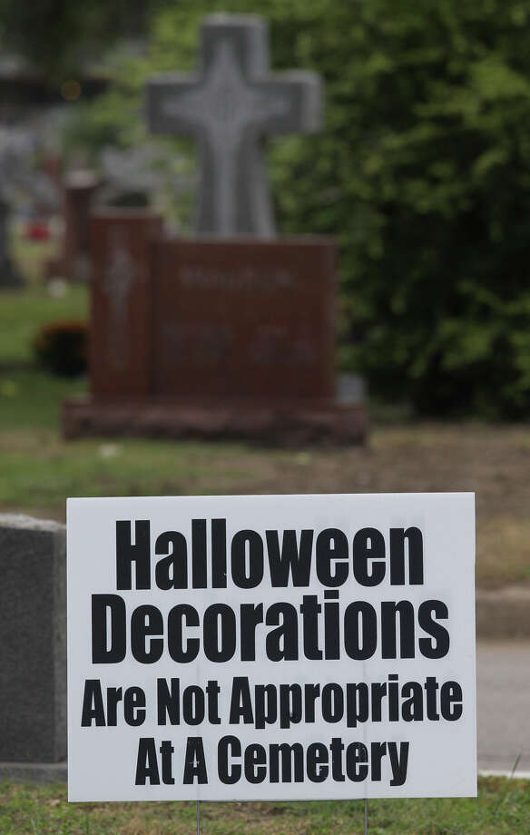 A sign at San Fernando Cemetery No. 2 attempts to discourage visitors from placing Halloween decorations at grave sites on Day of the Dead. Friday, Nov. 2, 2012. Photo: John Davenport, San Antonio Express-News / ©San Antonio Express-News/Photo Can Be Sold to the Public
