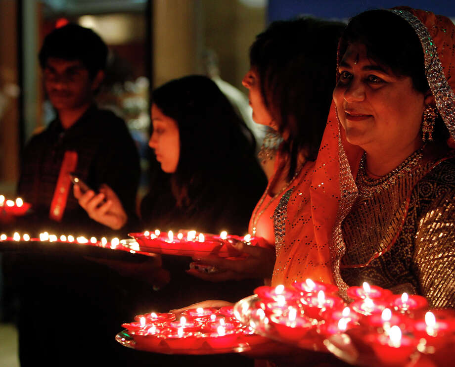 Participants hold plates of lit diyas, or candles, during Diwali, an Indian festival also known as the festival of lights, at Hemisfair Plaza on Saturday, Nov. 6, 2010. Diyas signify the triumph of good over evil. Photo: Michael Miller, San Antonio Express-News / mmiller@express-news.net