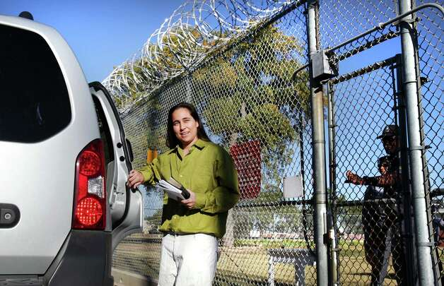 Anna Vasquez opens the door to a relative's car as prison guards at the Crain Unit in Gatesville close the prison gate behind her as she is released on parole after serving 12 and a half years.  Vasquez is one of the four San Antonio women fighting to clear their names in the 1994 sexual assault of two sisters. Friday, Nov. 2, 2012. Photo: Bob Owen, San Antonio Express-News / © 2012 San Antonio Express-News