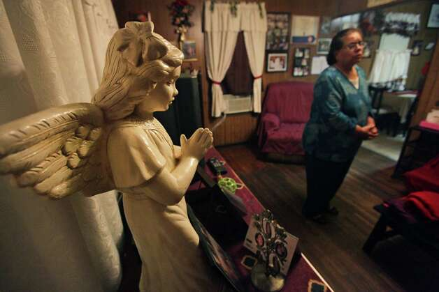 A statue of a praying angel stands near Maria Vasquez in her living room where Vasquez prayed daily for her daugter Anna Vasquez, one of four San Antonio women fighting to clear their names in the 1994 sexual assault of two sisters.  Anna was  released from prison on parole on Nov. 2, 2012, from the Crain Unit in Gatesville after serving 12 and a half years. Photo: Bob Owen, San Antonio Express-News / © 2012 San Antonio Express-News