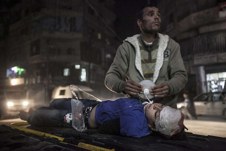 An 8-year-old Syrian girl struggles for life outside a hospital after she arrived badly wounded in an aerial attack by government forces in the Bab al-Neyrab neighborhood in Aleppo. Photo: Narciso Contreras, Associated Press
