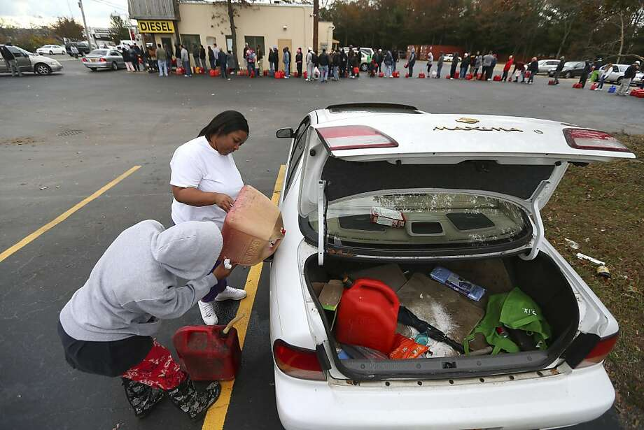 Joanne Moore puts gas in her car the old-fashioned way after waiting more than two hours in line at a gas station in Medford, N.Y., hard hit by the storm. Photo: Chang W Lee, New York Times