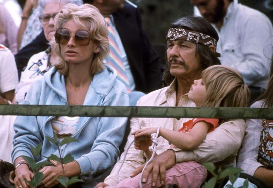 """Tough guy action star Charles Bronson began his popular vigilante """"Death Wish"""" movies in 1974. And only Bronson could pull off this long-haired, head-banded, mustachioed look. He's at the 1970 Olympic Games in Montreal with then-wife Jill Ireland and their daughter. Bronson died in 2003. Photo: STF, / / 2012 AFP"""