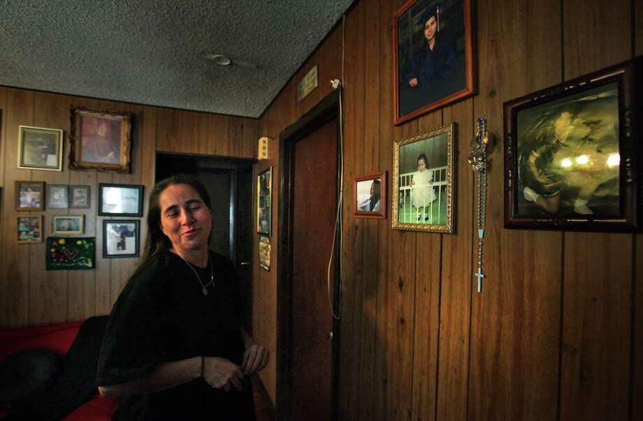 "Anna Vasquez, released from prison on Nov. 2, 2012, stops at the ""Anna Wall"" in her mother's home, joking that the photo of her in a crib as a baby, was the first picture of her behind bars. Photo: Bob Owen, San Antonio Express-News / © 2012 San Antonio Express-News"