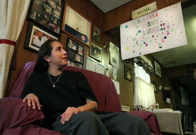 Anna Vasquez, just home after serving 12 and a half years in prison, admires family photos on the walls in her mother's home.  Vasquez, one of four San Antonio women fighting to clear their names in the 1994 sexual assault of two sisters, was released from prison at the Crain Unit in Gatesville, TX, on parole on Nov. 2, 2012. Photo: Bob Owen, San Antonio Express-News / © 2012 San Antonio Express-News