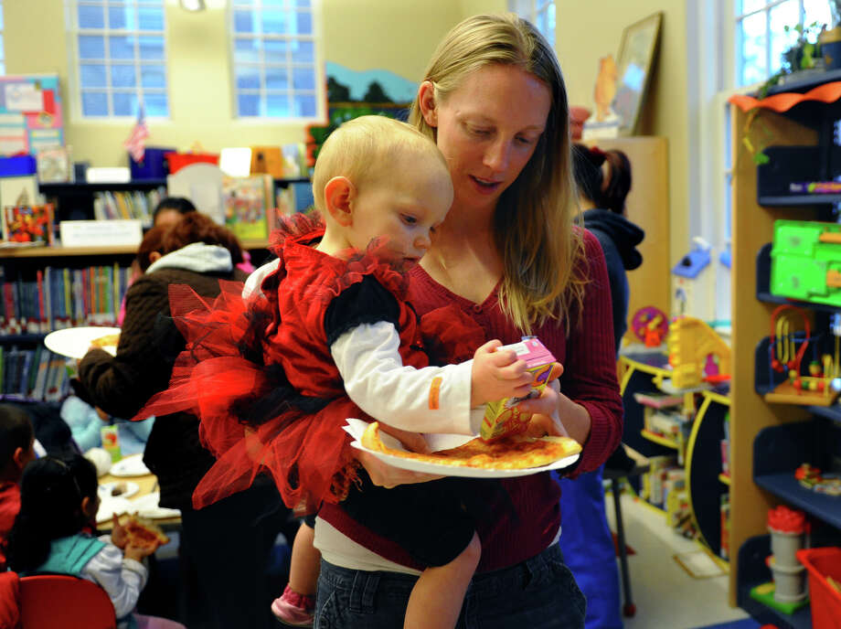 Gloria Nash and her daughter Evangelina, 16 months, enjoy the Fourth Annual Black Rock Halloween Parade and Block Party which started at Ellsworth Field and ended at the Black Rock Branch Library for snacks in the Black Rock section of Bridgeport, Conn. on Friday November 2, 2012.  The event was organized by the library and the Black Rock chapter of the Rotary Club. Photo: Christian Abraham / Connecticut Post