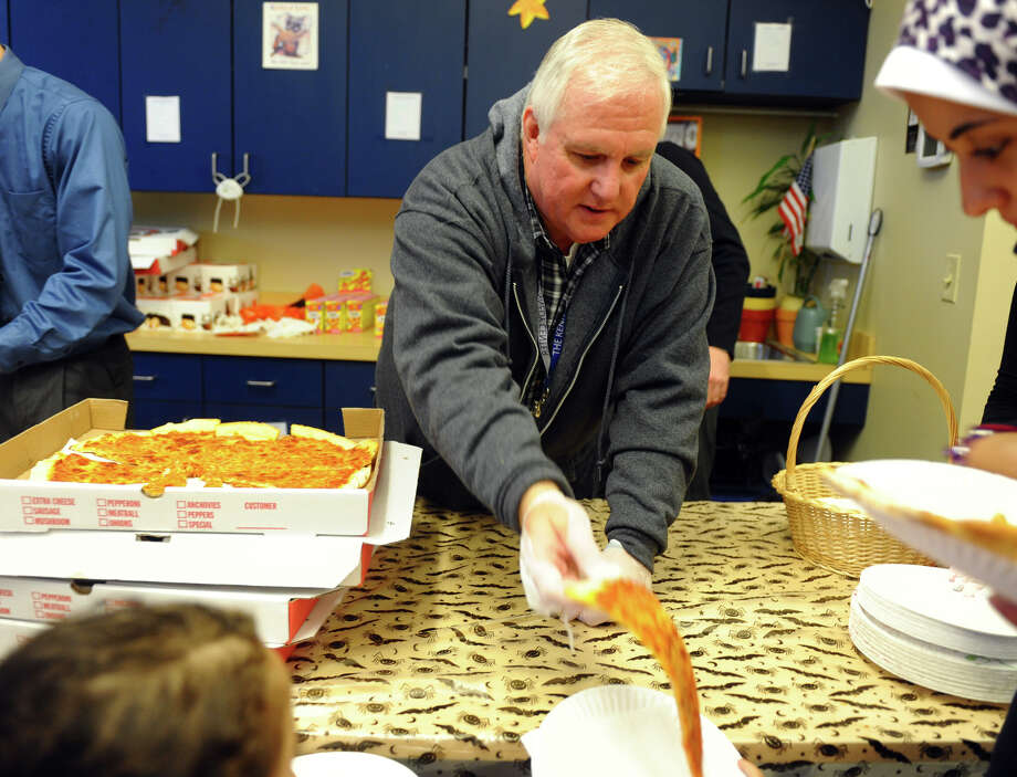 Ratary Club volunteer Charles Priddle serves pizza during the Fourth Annual Black Rock Halloween Parade and Block Party which started at Ellsworth Field and ended at the Black Rock Branch Library for snacks in the Black Rock section of Bridgeport, Conn. on Friday November 2, 2012. The event was organized by the library and the Black Rock chapter of the Rotary Club. Photo: Christian Abraham / Connecticut Post