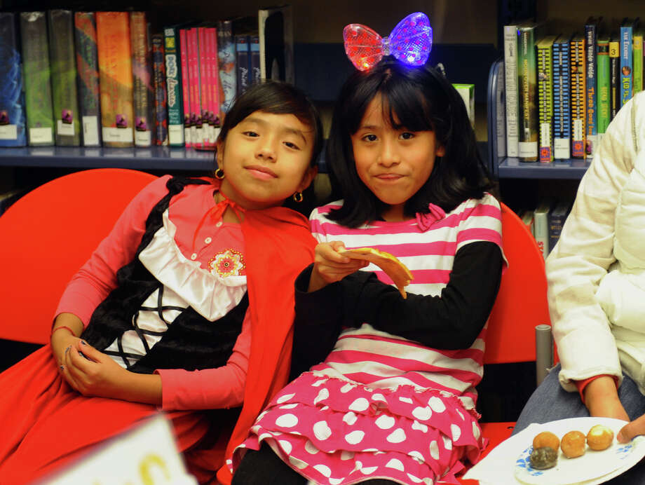 Sara Mani, 8, left, and her friend Madiam Mena, 7, enjoy snacks during the Fourth Annual Black Rock Halloween Parade and Block Party which started at Ellsworth Field and ended at the Black Rock Branch Library for snacks in the Black Rock section of Bridgeport, Conn. on Friday November 2, 2012. The event was organized by the library and the Black Rock chapter of the Rotary Club. Photo: Christian Abraham / Connecticut Post