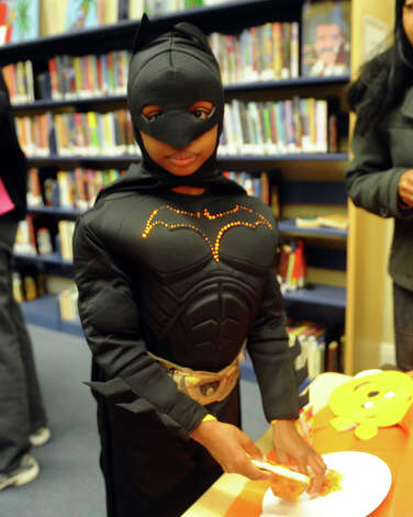 Nicholas Crawford, 8, plays Batman, during the Fourth Annual Black Rock Halloween Parade and Block Party which started at Ellsworth Field and ended at the Black Rock Branch Library for snacks in the Black Rock section of Bridgeport, Conn. on Friday November 2, 2012. The event was organized by the library and the Black Rock chapter of the Rotary Club. Photo: Christian Abraham / Connecticut Post