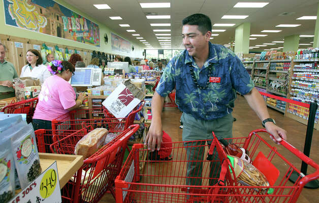 Manager Jorge Macias tries to help move customers through the checkout lanes as Trader Joe's at 350 East Basse Road opens for business on November 2, 2012. Photo: Tom Reel, San Antonio Express-News / ©2012 San Antono Express-News