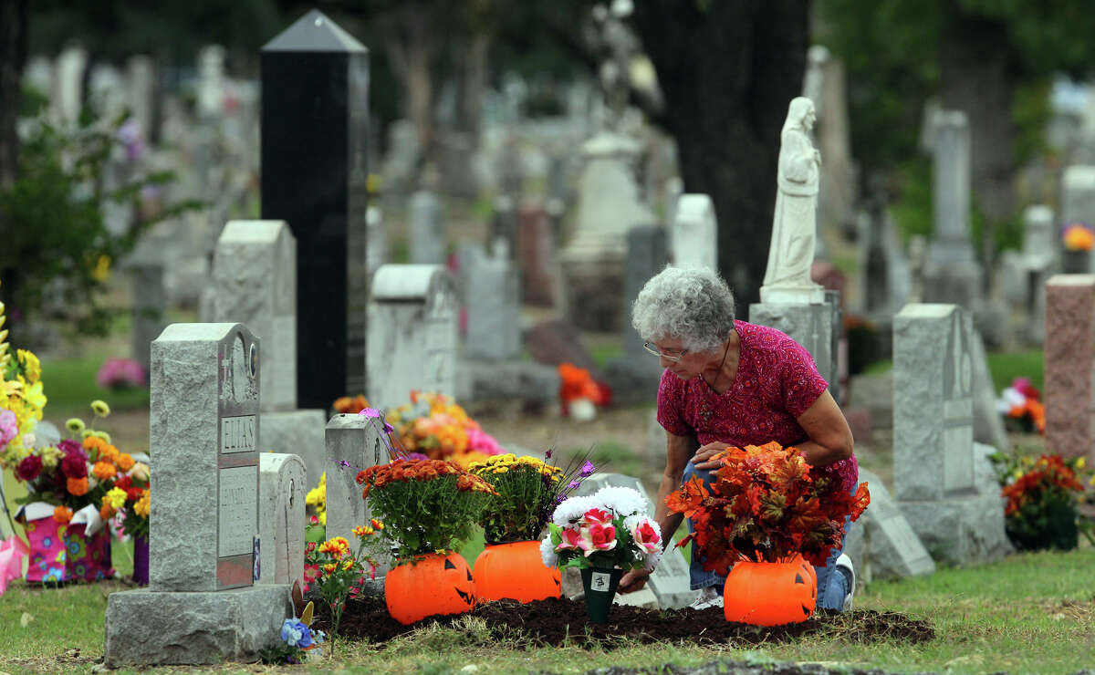 Elisa Van Tine tends to the graves of her mother and grandmother at San Fernando Cemetery No. 2 on the Catholic feast known as All Soul's Day or Dia de los Muertos, Friday, Nov. 2, 2012.