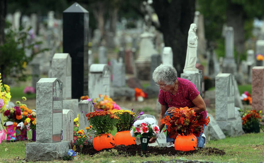 "Elisa Van Tine tends to the graves of her mother and grandmother at San Fernando Cemetery No. 2 on the Catholic feast known as All Soul's Day or Dia de los Muertos, Friday, Nov. 2, 2012. ""Who's going to do this when I'm gone?"" Van Tine said. Photo: JOHN DAVENPORT, San Antonio Express-News / ©San Antonio Express-News/Photo Can Be Sold to the Public"