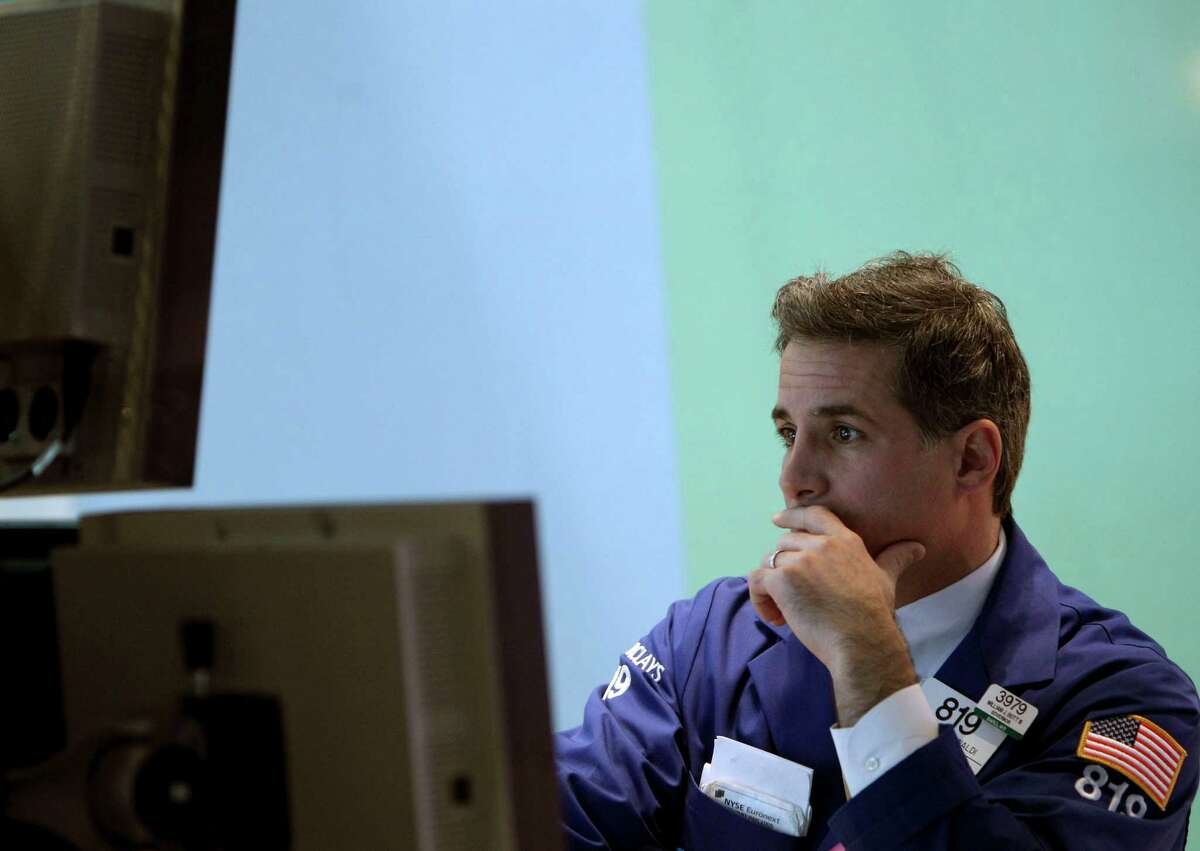 FILE - In this Wednesday, Oct. 31, 2012, file photo, a trader works on the floor at the New York Stock Exchange in New York. Wall Street was poised for a steady opening Friday Nov. 2, 2012, with both Dow futures and the S&P 500 futures down 0.1 percent. How they actually open will likely hinge on the jobs figures which are released an hour before the opening bell. (AP Photo/Seth Wenig, File)