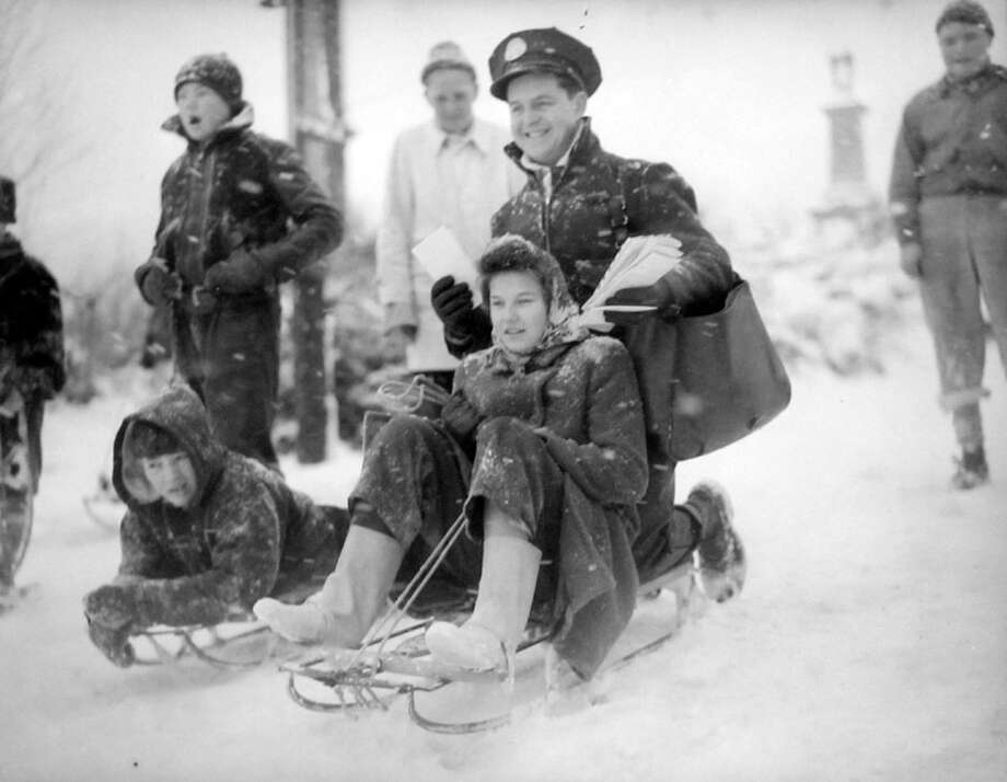 "This picture, taken Jan. 20, 1943, ran on the front page of the following day's P-I. The original caption read: ""Despite heavy drifts of snow, Oscar Pennington, Seattle postman, delivers his morning mail with the timely assistance of Joyce Baldwin, twelve, and her sled."" A specific photographer was not credited. (Copyright MOHAI, Seattle Post-Intelligencer Collection, PI28401. Click for reproductions.) Photo: -"