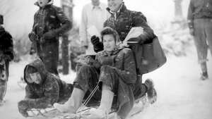 "This picture, taken Jan. 20, 1943, ran on the front page of the following day's P-I. The original caption read: ""Despite heavy drifts of snow, Oscar Pennington, Seattle postman, delivers his morning mail with the timely assistance of Joyce Baldwin, twelve, and her sled."" A specific photographer was not credited."