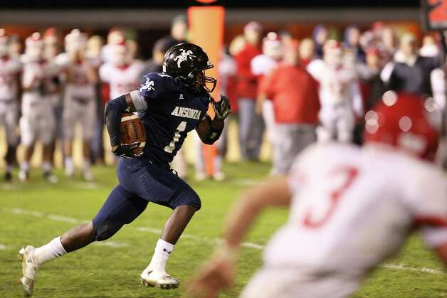 Mike Ross Connecticut Post freelance - Ansonia High School's # 1 JaiQuan McKnight inetecepts the ball and make his way upfield during Friday evening game between Wolcott High School. Photo: Mike Ross / Connecticut Post Freelance