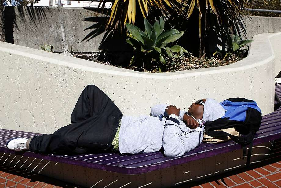 Complaints about people sleeping, like this person in September, were among the reasons the benches were removed. Photo: Liz Hafalia, The Chronicle