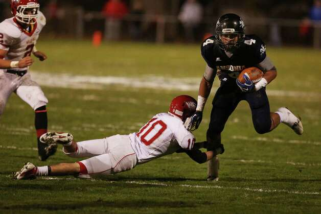 Mike Ross Connecticut Post freelance - Ansonia High School's # 4  JaiQuan McKnight moves the ball and escapes the tackle from Wolcott High School's # 10 Chris Petillo during first half action on Friday evening. Photo: Mike Ross / Connecticut Post Freelance
