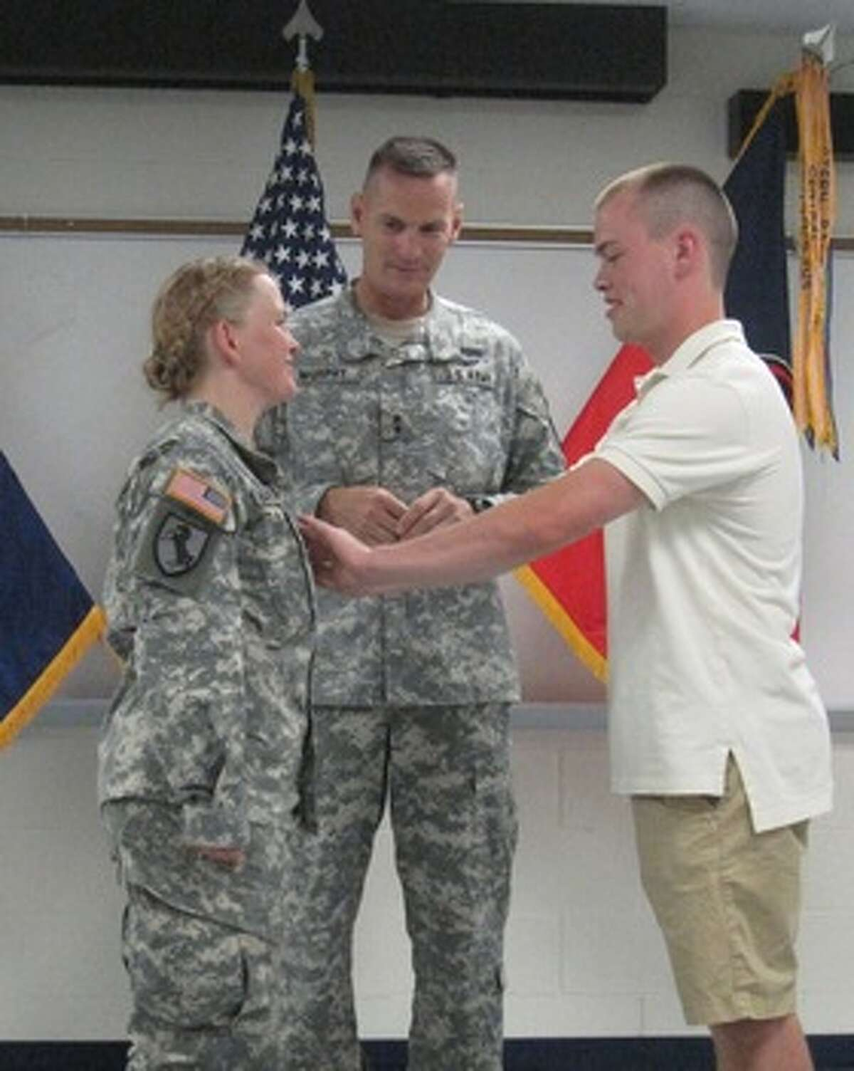 KIM DEAL Maj. General Patrick Murphy, adjutant general of New York, looks on as Col. Tammy Mandwelle?s son Jordan Mandwelle puts her new rank in place during a ceremony in Syracuse.