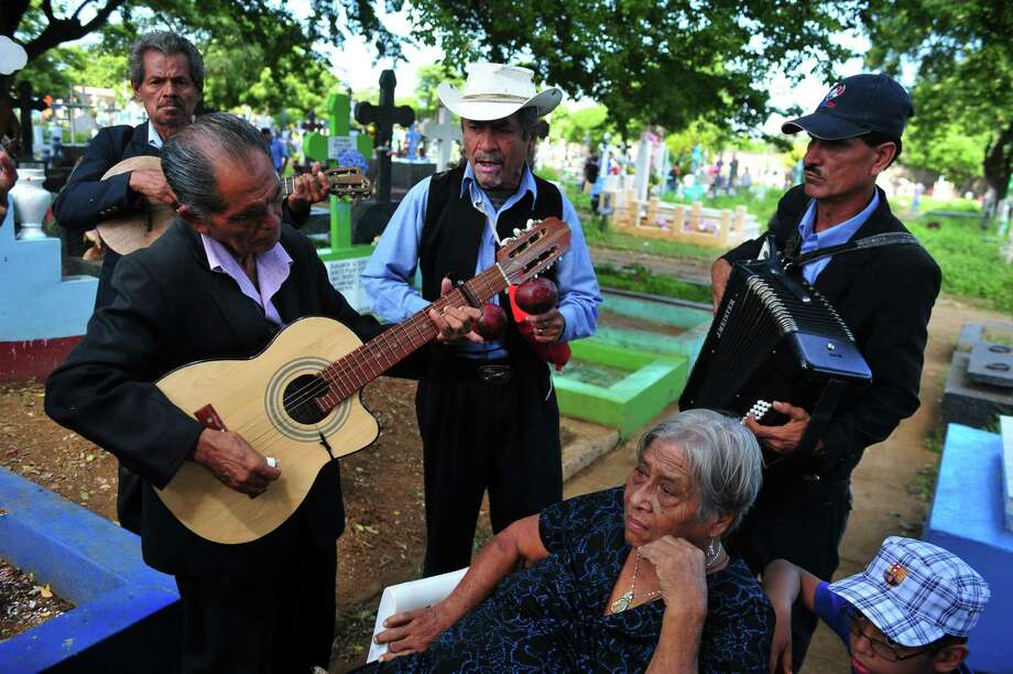 Musicians play instruments and sing for a woman who hired their services to honor her deceased husband at the General Cemetery in Managua during All Souls Day, on November 2, 2012. AFP PHOTO/Hector RETAMALHECTOR RETAMAL/AFP/Getty Images Photo: HECTOR RETAMAL, Staff / AFP