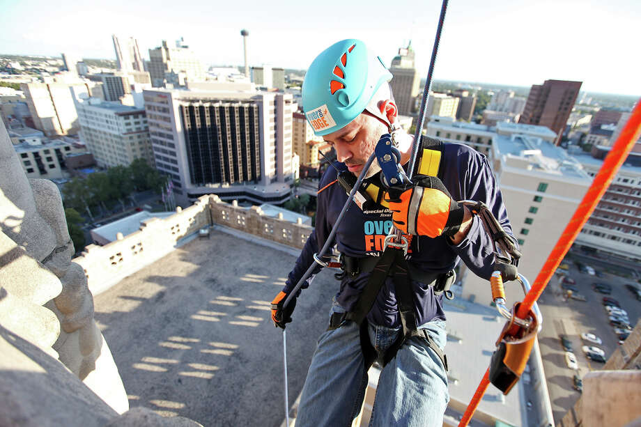 CVS Caremark employee Damian Tenorio rappels off the Milam Building during the Special Olympics Texas Over the Edge event held Friday Nov. 2, 2012 and continues on Saturday Nov. 3, 2012. Participants should be 18 years or older by the day of the event, weigh between 110 to 300 lbs., and must raise a minimum of $1,000. No previous rappelling experience is required, Over the Edge rope experts and area SWAT teams will assist you. The event will be held in Austin, San Antonio, Dallas, and Houston. For more information visit www.sotx.org/overtheedge. Photo: Edward A. Ornelas, San Antonio Express-News / © 2012 San Antonio Express-News