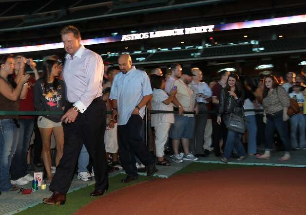 Former Houston Astros pitcher Roger Clemens makes his way into the VIP area at Minute Maid Park, Friday, Nov. 2, 2012, in Houston, before the Houston Astros unveiled their new logo, uniform, and mascot.