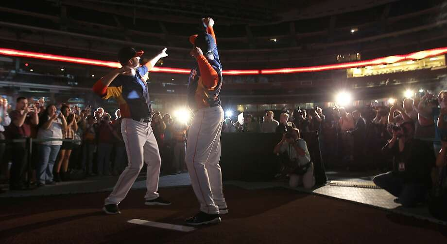 Houston Astros Jordan Lyles, left, and minor leaguer Jonathan Singleton, right, model one of the new Astros uniforms at Minute Maid Park, Friday, Nov. 2, 2012, in Houston, as the Houston Astros unveiled their new logo, uniform, and mascot.