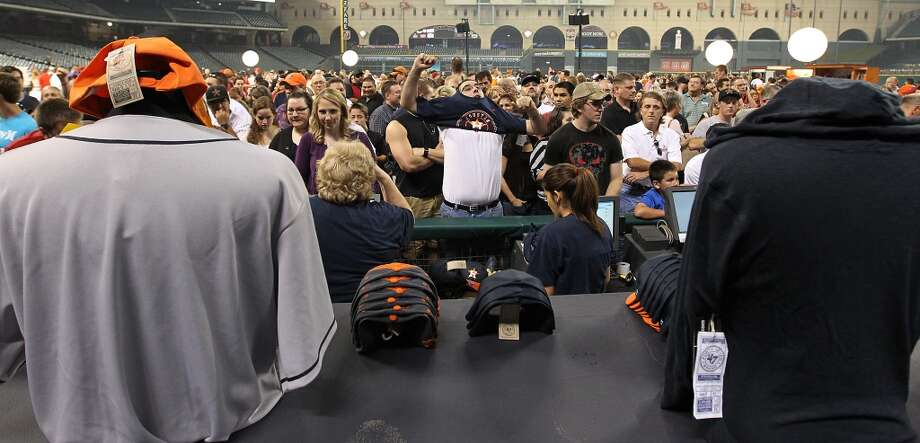 Josh Otto, of Houston, changes into his new Houston Astros t-shirt while in line, as fans lined up to buy t-shirts and hats with the new Houston Astros logo on the field at Minute Maid Park, Friday, Nov. 2, 2012, in Houston, as the Houston Astros unveiled their new logo, uniform, and mascot.