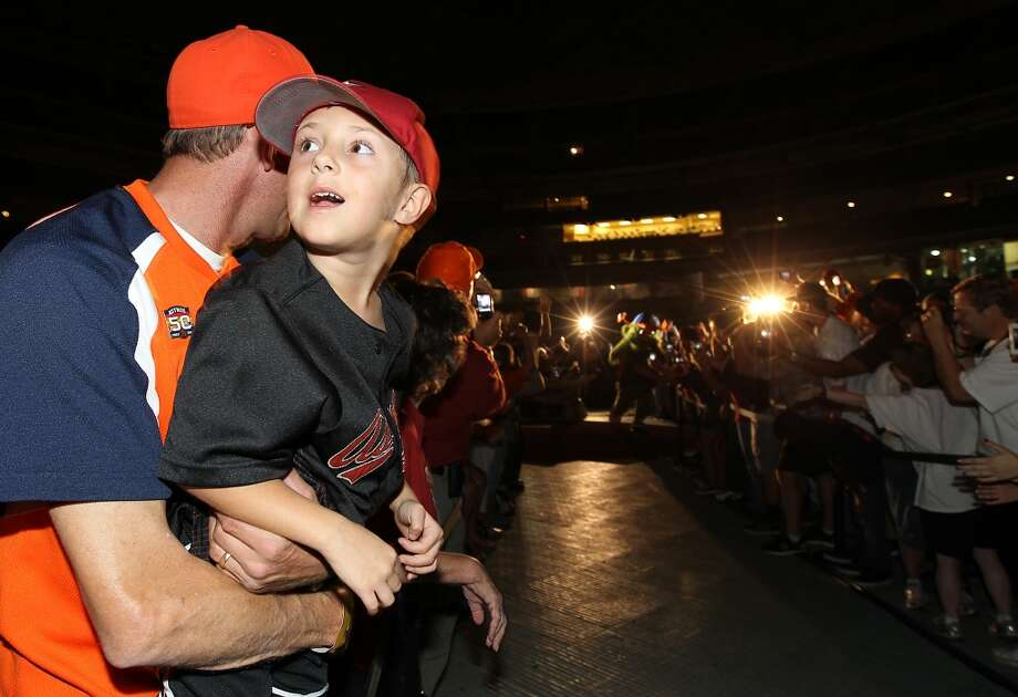 Michael McKay holds his son, Morgan, 6, as they wait for Orbit, the Houston Astros new mascot to make his way onto the stage at Minute Maid Park, Friday, Nov. 2, 2012, in Houston, as the Houston Astros unveiled their new logo, uniform, and mascot. Orbit was brought back as the official mascot from the 1990-1999 seasons, after he was replaced from 2000-2012 by Junction Jack.