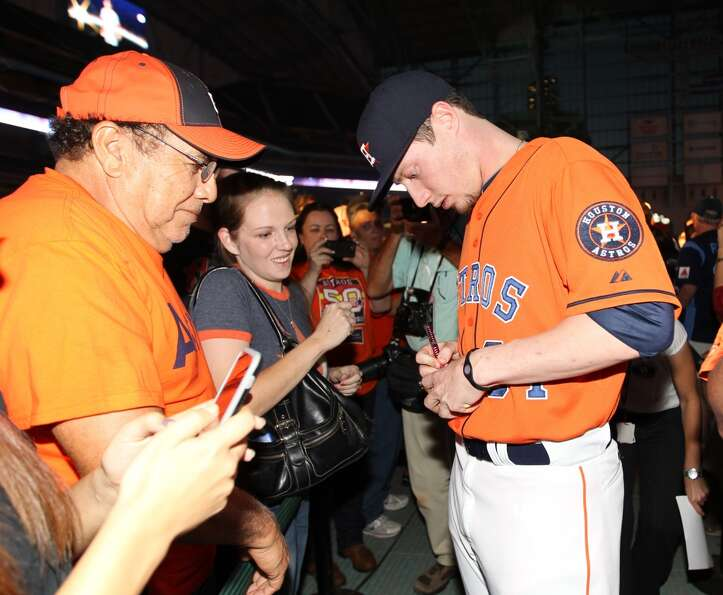 Houston Astros pitcher Lucas Harrell signs autographs for fans wearing one of the new uniforms at Mi