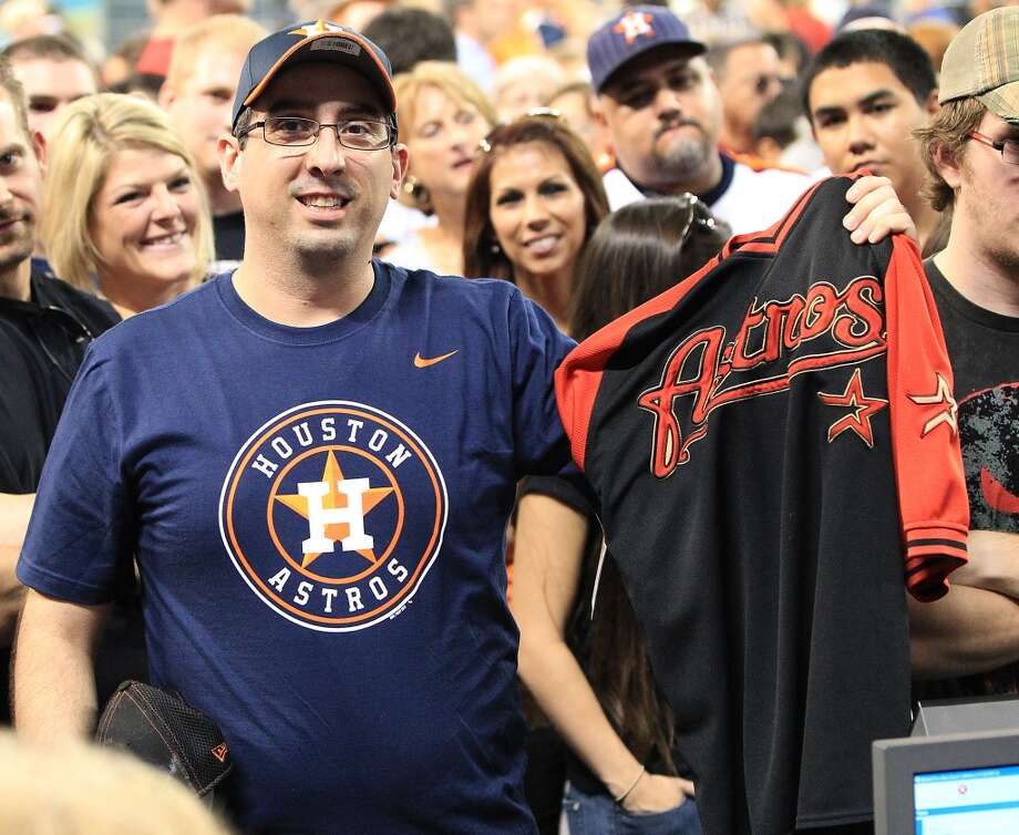 Houston Astros fan, Josh Otto shows off his t-shirt with the new Astros logo as he holds up his t-shirt with old logo, as he and other fans lined up to buy the newly unveiled merchandise at Minute Maid Park, Friday, Nov. 2, 2012, in Houston, after a ceremony where the Astros unveiled their new logo, uniform, and mascot.