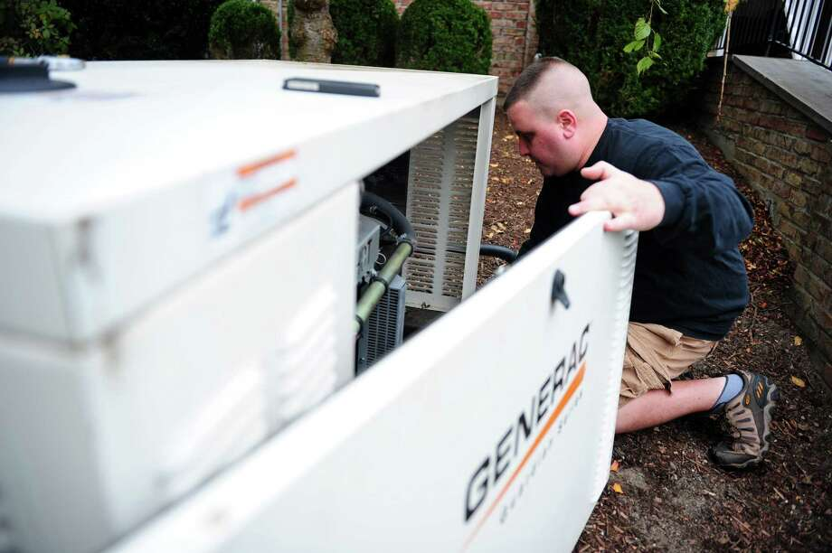 Pete Mazzucco, owner of Mazzucco Electric in Fairfield, performs maintenance on a generator at a home on Queen's Grant Road in Fairfield, Conn. Friday, Nov. 2, 2012. Photo: Autumn Driscoll / Connecticut Post