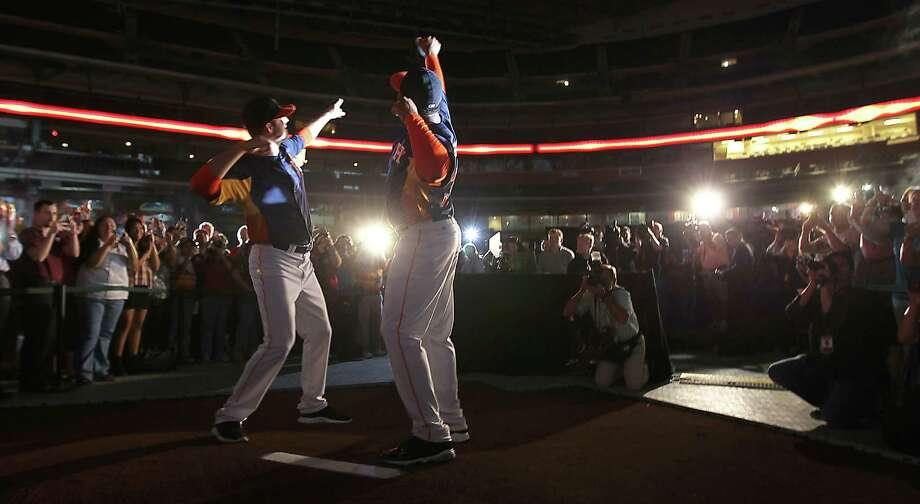 Houston Astros Jordan Lyles, left, and minor leaguer Jonathan Singleton, right, model one of the new Astros uniforms at Minute Maid Park, Friday, Nov. 2, 2012, in Houston, as the Houston Astros unveiled their new logo, uniform, and mascot. Photo: Karen Warren, Houston Chronicle / © 2012  Houston Chronicle