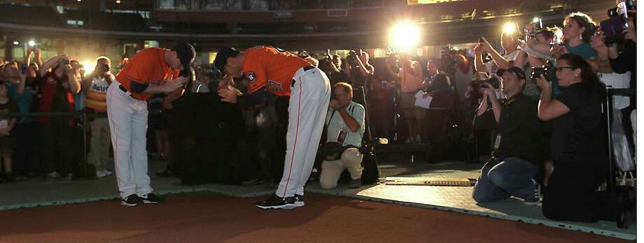 Houston Astros' Lucas Harrell, left, and Jarred Cosart, right, bow to each other as they model one of the uniforms in front of fans at Minute Maid Park, Friday, Nov. 2, 2012, in Houston, as the Houston Astros unveiled their new logo, uniform, and mascot. Photo: Karen Warren, Houston Chronicle / © 2012  Houston Chronicle