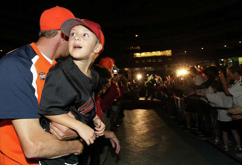 Michael McKay holds his son, Morgan, 6, as they wait for Orbit, the Houston Astros new mascot to make his way onto the stage at Minute Maid Park, Friday, Nov. 2, 2012, in Houston, as the Houston Astros unveiled their new logo, uniform, and mascot. Photo: Karen Warren, Houston Chronicle / © 2012  Houston Chronicle