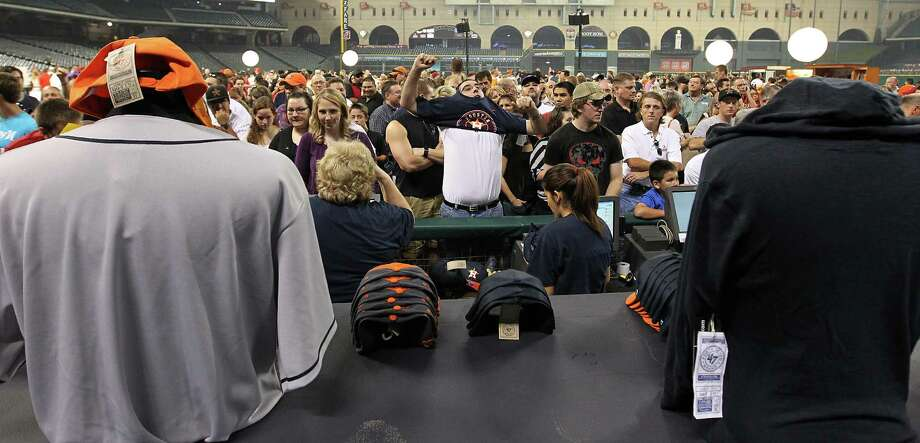 Josh Otto, of Houston, changes into his new Houston Astros t-shirt while in line, as fans lined up to buy t-shirts and hats with the new Houston Astros logo on the field at Minute Maid Park, Friday, Nov. 2, 2012, in Houston, after the Houston Astros unveiled their new logo, uniform, and mascot. Photo: Karen Warren, Houston Chronicle / © 2012  Houston Chronicle