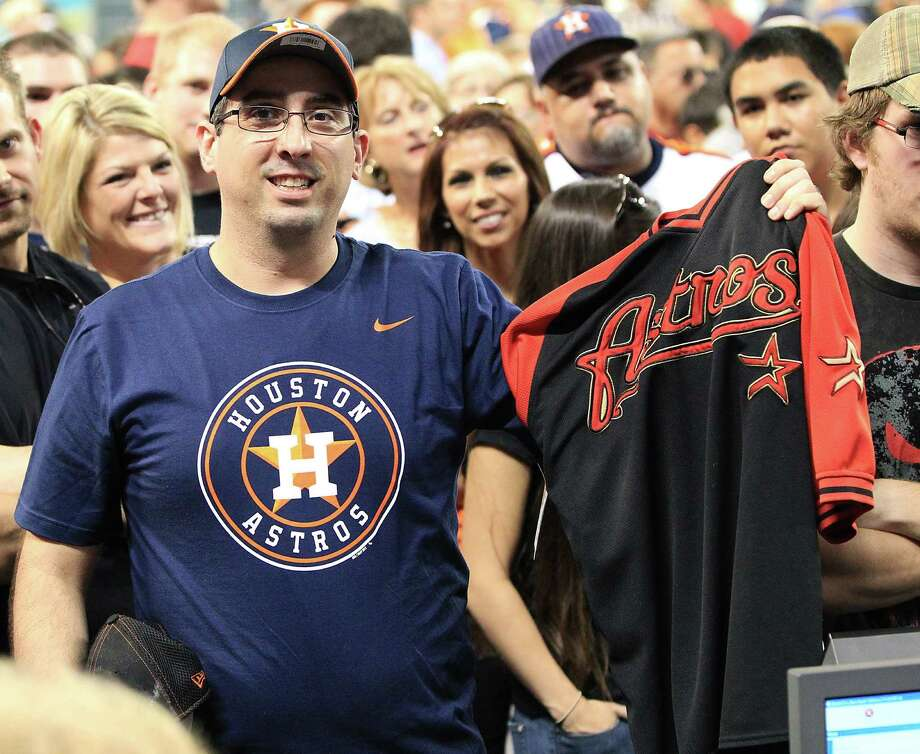 Houston Astros fan, Josh Otto shows off his t-shirt with the new Astros logo as he holds up his t-shirt with old logo, as he and other fans lined up to buy the newly unveiled merchandise at Minute Maid Park, Friday, Nov. 2, 2012, in Houston. Photo: Karen Warren, Houston Chronicle / © 2012  Houston Chronicle