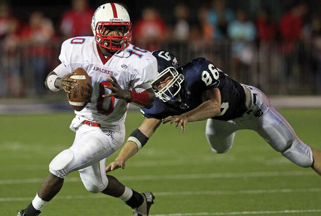 Apache quarterback Chad Tatum avoids the diving tackle of Matthew Gaston as Central Catholic hosts Antonian at Benson Stadium on November 2, 2012. Photo: Tom Reel, Express-News / ©2012 San Antono Express-News